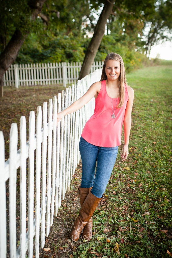 senior girl standing in a field pittsburgh by cemetery fence pink shirt boots